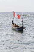 Typical African Fishing Boat With Red And White Flag In The Water