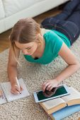 Focused young woman lying on floor using tablet to do her assignment in living room