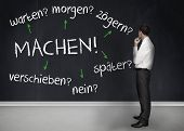 Thoughtful businessman looking at words machen warten morgen zogern spater verschieben nein on a chalkboard