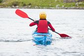 stock photo of kayak  - Woman rowing in a kayak in a cold lake - JPG