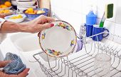 Cropped image of senior woman arranging plate in rack at kitchen counter
