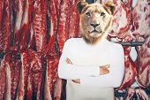 Butcher with a lion head with arms folded standing in front of red meat