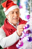 Male owner in Santa hat decorating Christmas tree at store