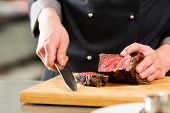 stock photo of hand cut  - Chef in hotel or restaurant kitchen cooking - JPG