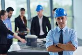 image of engineering construction  - business people group on meeting and presentation  in bright modern office with construction engineer architect and worker looking building model and blueprint planbleprint plans - JPG