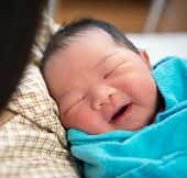 picture of bassinet  - Newborn Asian baby girl smiling and fall asleep in mother - JPG