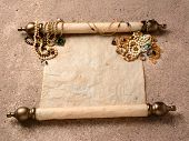 Pirates Booty. An ancient scroll laying on beach sand with jewelry scattered on it upper end. The sc