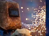 foto of construction industry  - Heavy industry welder worker in protective mask hand holding arc welding torch working on metal construction - JPG