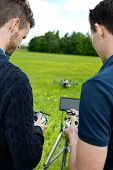 Rear view of young engineers operating UAV helicopter with remote controls in park