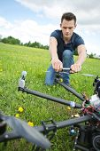 Young technician crouching while fixing propeller of surveillance drone in park