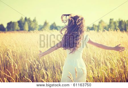 Beauty Girl Outdoors enjoying nature. Beautiful Teenage Model girl in white dress running on the Spr poster