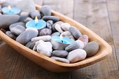Wooden bowl with Spa stones, sea shells and candles on wooden background
