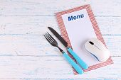 Computer mouse with menu and cutlery on wooden background