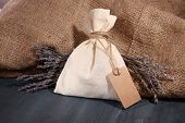 Textile sachet pouch with dried lavender flowers on wooden table, on sackcloth background