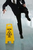 Businessman slipping on wet floor in front of caution sign in hallway