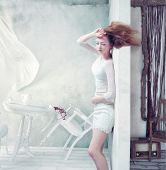 beautiful woman at the wall, windswept. creative concept
