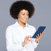 Beautiful African American woman using her tablet surfing the internet and looking at information on the screen with a speculative disbelieving expression
