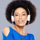 Gorgeous beautiful young African American woman with a frizzy afro hairstyle listening to music on h