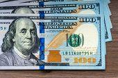 New hundred Dollar Bills on wooden background
