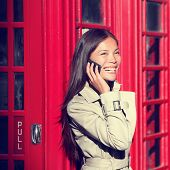 London woman on smart phone by red phone booth. Young casual female business woman having conversati