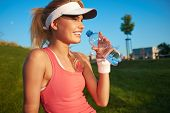 fitness and lifestyle concept - woman drinking water after doing sports outdoors