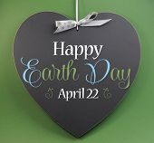 Happy Earth Day April 22, Message Sign Greeting On A Heart Shaped Blackboard Against A Green Backgro