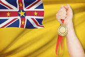 Medal In Hand With Flag On Background - Niue