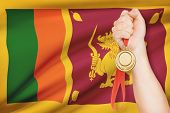 Medal In Hand With Flag On Background - Democratic Socialist Republic Of Sri Lanka