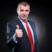 successful old business man making the ok thumbs up hand sign on dark studio background