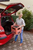a young woman lifts a crate of bottles from their car. real life prevents back pain and herniated di