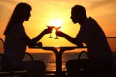 Man And Woman Clink Glasses On Sunset Outside