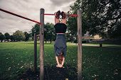 Woman Dangling From Pullup Bars