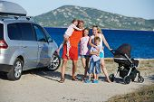 Big Family. Parents with four children on sea, lake or ocean shore at vacation