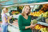 woman choosing pineapple during shopping at fruit vegetable supermarket