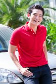 Asian man standing in front of new car