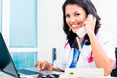Asian female doctor working and telephoning in office or medical practice