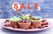 Concept of discount. Tasty cupcakes with butter cream, on plate, on color wooden background