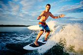 Active young man spending leisure surfing on waves