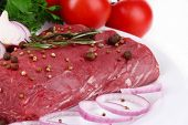 Raw beef meat with vegetables on plate close up