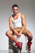 fit casual man in undershirt sitting on a cube in studio