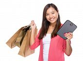 Happy woman with shopping bag and tablet