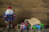 Santa Claus On Wooden Background With Colorful Presents