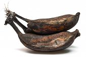 Black Overripe Bananas On A White Background
