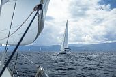 Yachting in the wind through the waves. Sailing regatta. Luxury yachts.