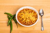Chili With Cheese On Wood Table With Cayenne Peppers