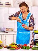Mature woman preparing dinner at kitchen.