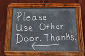 Please use other door Sign on a door in chalk pen.