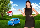 Woman with key in hand. Small automobile and house on grass