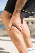 Fit man gripping his injured calf muscle on a sunny day