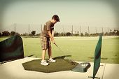 Young boy at golf driving range with a retro instagram look.